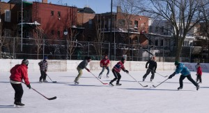 Outdoor shinny game in a Mile End park. Who is that dashing guy in blue trying to reach for the puck? Ha ha. Gazette photo by Allen McInnis.
